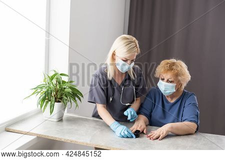 Medical Help At Home. Woman Doctor In A Medical Mask Measures The Patients Pulse And Oxygen Saturati