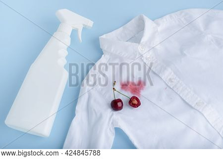 Juice Stain With Stain Remover Spray For Clothes. Isolated On A Blue Background. Top View. Isolated