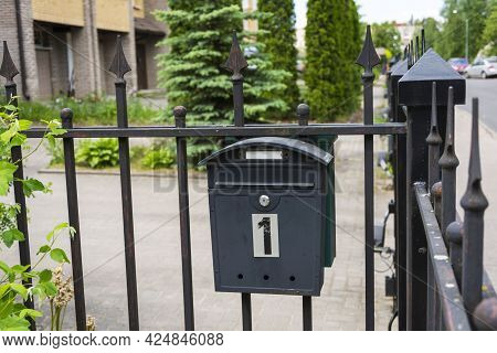 Mailbox Of A Private House, A Black Metal Mailbox Installed On The Fence Grid Of A House.