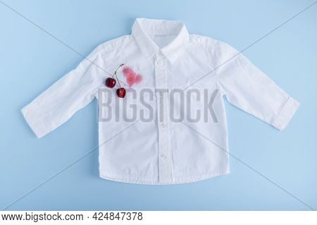 Dirty Stain Of Cherry Juice On White Clothes. Isolated On Blue Background. High Quality Photo