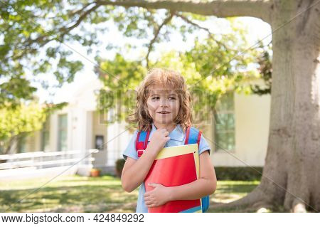 Child With Rucksacks Standing In The Park Near School. Pupils With Books And Backpacks Outdoors. Sch