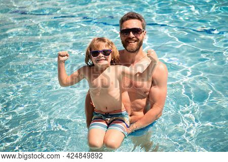 Father And Son Swimming In Pool, Summer Family Vacation. Pool Party. Child With Dad Playing In Swimm