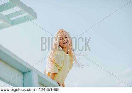 Portrait Of Young Pretty Blond Girl With Long Hair In Yellow Summer Sweater Posing At The Blue Lifeg