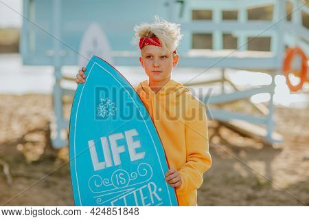 Cute Blond Teen Boy In Orange Hoodie And Red Headband Posing And Making Faces With Blue Surfboard Ag