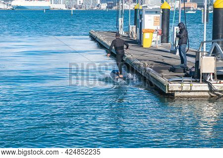 Auckland New Zealand - June 17 2021;foil Boarder Landing At Pier After Tow Around Bay Behind Jet-ski