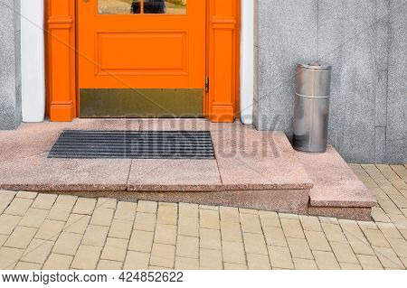 Granite Threshold With Foot Mat Near Orange Wooden Front Door With Iron Trash Can Near Building Faca
