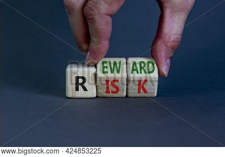 Risk Or Reward Symbol. Businessman Turns Wooden Cubes And Changes The Word 'risk' To 'reward'. Beaut
