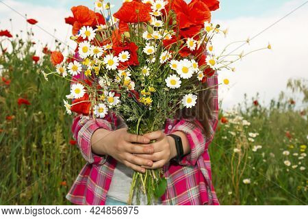 The Girl Stands Against The Background Of Wild Flowers And Holds A Bouquet Of Poppies And Daisies In
