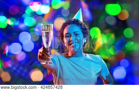 birthday, celebration and nightlife concept - happy smiling young african american woman in party cap with glass of champagne in ultraviolet neon lights over bokeh background