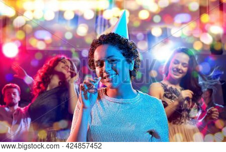 birthday, celebration and nightlife concept - happy smiling young african american woman in party cap with blower in ultraviolet neon lights over nightclub background