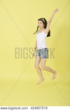 Happy Woman Jumping On Yellow Summer Backgrounds