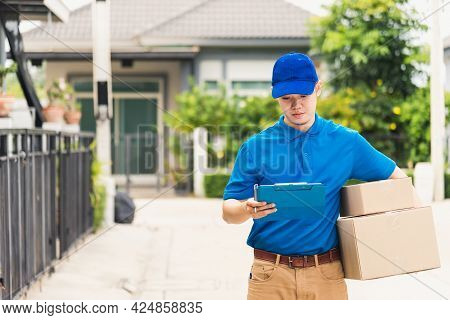 Asian Young Delivery Man Courier In Uniform Hold Parcel Post Boxes Service Shipment And Walking Find
