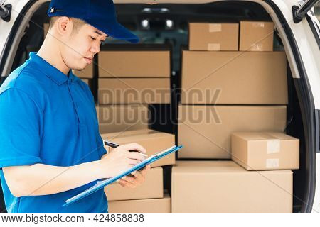 Asian Young Delivery Man Courier In Uniform Hold Documents Clipboard Checking List Parcel Post Boxes