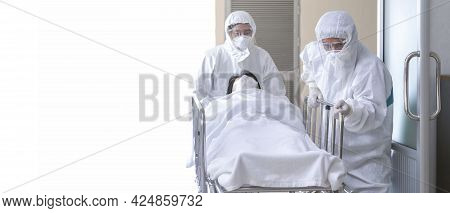 Asian Male Nurse And Doctor Wearing Ppe Suit And Face Mask Pushing Stretcher Gurney Bed With Serious