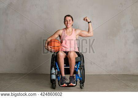 Basketballer in a wheelchair flexing her arms