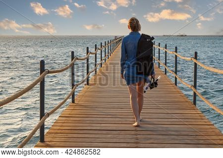 Woman With A Dive Mask And A Snorkel Going On A Wooden Pier Extending Into The Sea At Sunrise.
