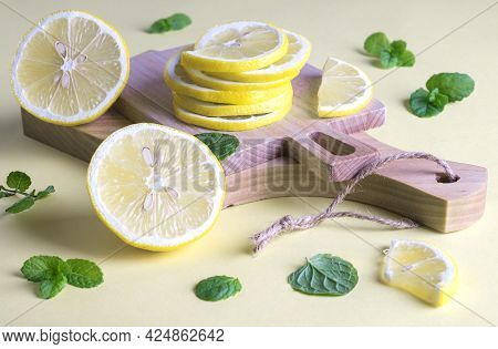 Two Small Kitchen Utensils Cutting Boards With Slices Of Ripe Fresh Lemon And Mint Leaves. Ingredien