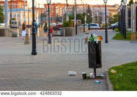 Overflowing Trash Can On The Sidewalk Pavement At Summer Daylight