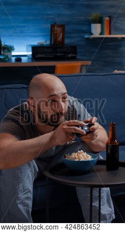 Competitive Determined Man Playing Videogame In Living Room At Night Focused Eating Popcorn Enjoying