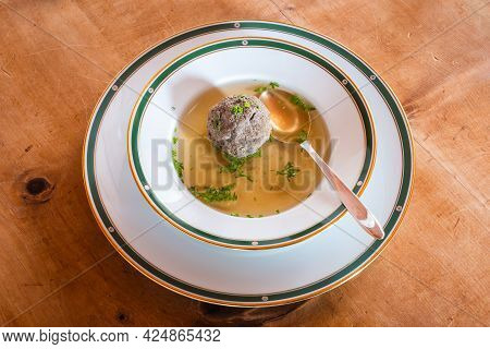 Leberknoedelsuppe, An Austrian Liver Dumpling Soup, A Beef Broth With Chives With Spoon