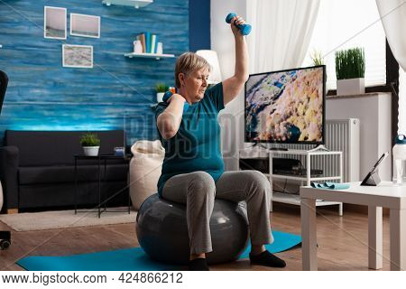 Focused Retirement Pensioner Sitting On Fitness Swiss Ball Raising Hand Streching Arm Muscle Doing H
