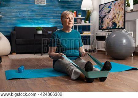 Retirement Senior Woman Sitting On Yoga Mat Stretching Legs Muscles Using Stretch Elastic Band Train