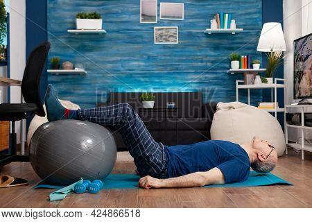 Retired Senior Sportman Sitting On Yoga Mat Practicing Warming Legs Up Exercises Using Swiss Ball St
