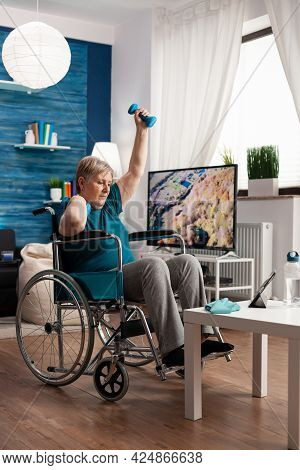 Invalid Senior Woman In Wheelchair Watching Gym Body Exercise On Tablet In Living Room Exercising Ar