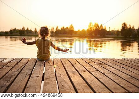 Silhouette Of A Child Sitting On The Wooden Pier And Enjoying Heat Summer Evening At The Lake At Sun