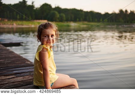 Smiling And Happy Baby Girl Sitting On A Pier At A Lake At The Summer Evening. Beauty In The Nature,