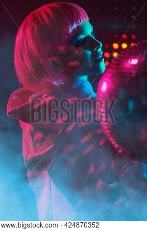 Night party style. Portrait a modern girl with bright glitter make-up and pink hair posing in the neon lights of the nightclub. Disco style.