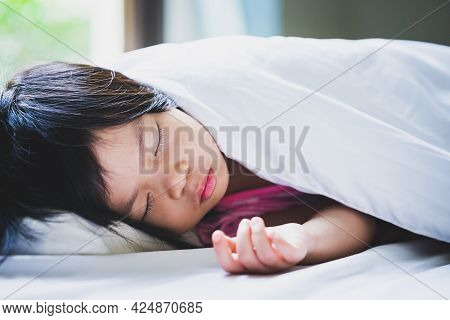 Asian Child Girl Sleeping On The White Soft Bed. In The Morning On Summer Time. Cute Children Lying
