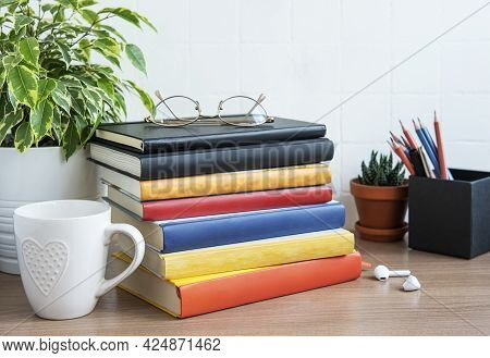 Stack Of Books On The Desktop. Various Book And Office Supplies On The Table