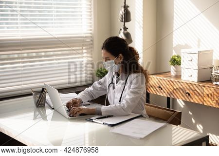 Female Doctor In Facemask Work On Computer In Clinic