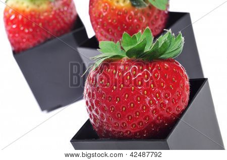 strawberries in black cubical bowls