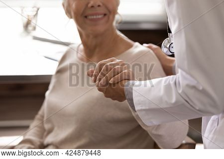 Close Up Of Female Nurse Help Old Woman Patient