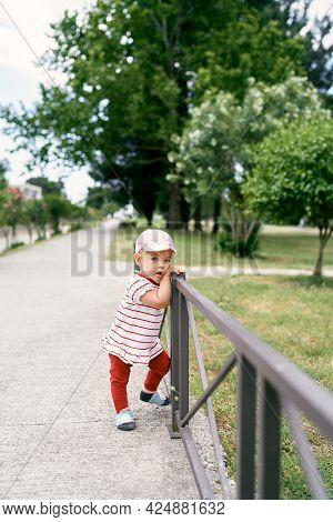 Little Girl In A Panama Hat Stands Leaning Against A Metal Fence In A Green Park