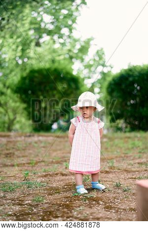 Little Girl In A Panama Hat Stands On The Lawn Against The Background Of Green Bushes