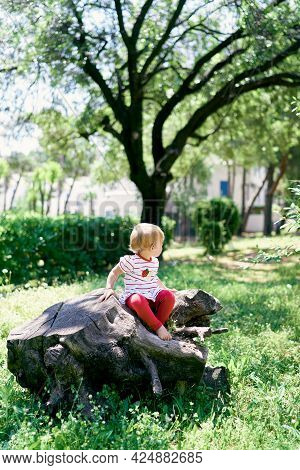 Little Barefoot Child Sits On A Tree Stump In A Green Park, Turning His Head