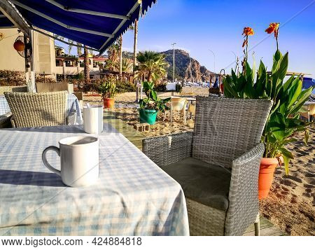 Two White Cups Sit On A Table With A Checkered Tablecloth And Wicker Chairs At A Beach Cafe In Alany