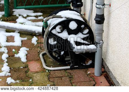 Light Grey Garden Hose With Hose Reel Mounted On Side Of Suburban Family House Wall Next To Homemade