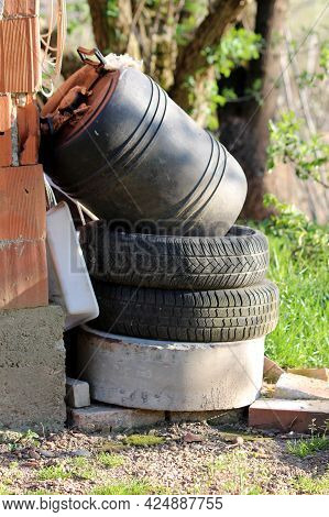 Pile Of Junk In Form Of Old Car Tyres Mixed With Construction Material And Heavily Used Small Black