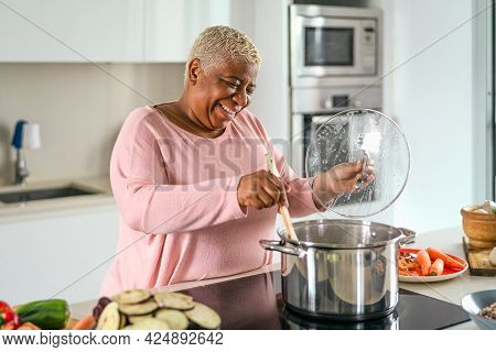 Happy Senior Woman Preparing Lunch In Modern Kitchen - Hispanic Mother Cooking For The Family At Hom