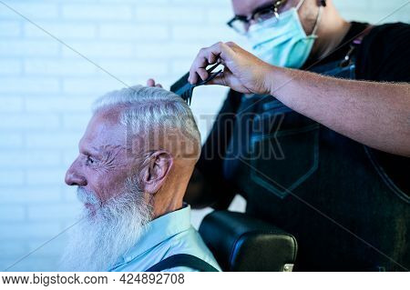 Male Hairdresser Cutting Hair To Beard Senior Client While Wearing Face Surgical Mask - Young Hairst