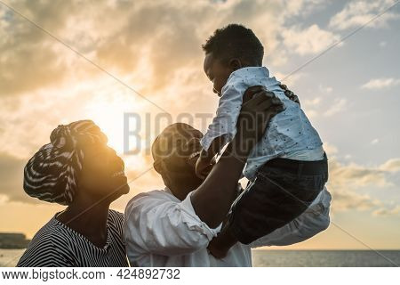 Happy African Family Having Fun On The Beach During Summer Holidays - Parents Love Concept