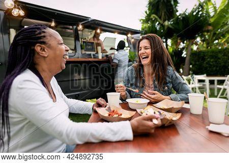 Happy Multiracial Senior Friends Having Fun Eating In A Street Food Truck