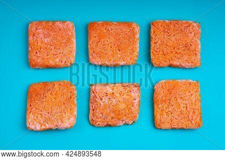 Orange Bricks Of Frozen Grated Carrots. Procurement Of Frozen Food. Semifinished.