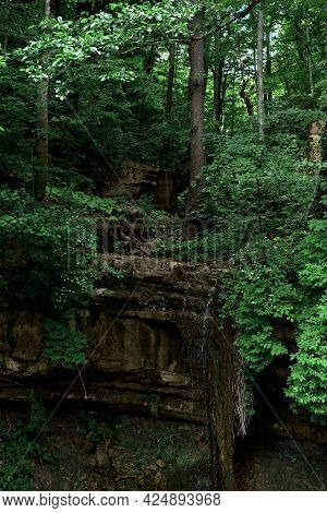 Small Waterfall Flows Down In Thin Stream From Rocky Rocks Among Dense Green Summer Forest. It Is Ar