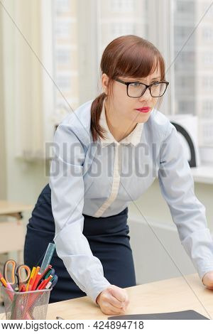 Young Strict Woman Boss In Glasses And A Blue Blouse In The Office At The Working Table Is Angry