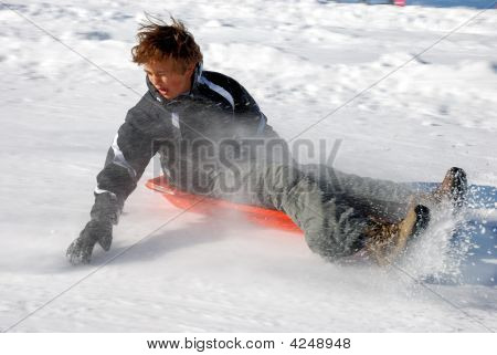Boy Braking The Sled While Sledding Down The Hill